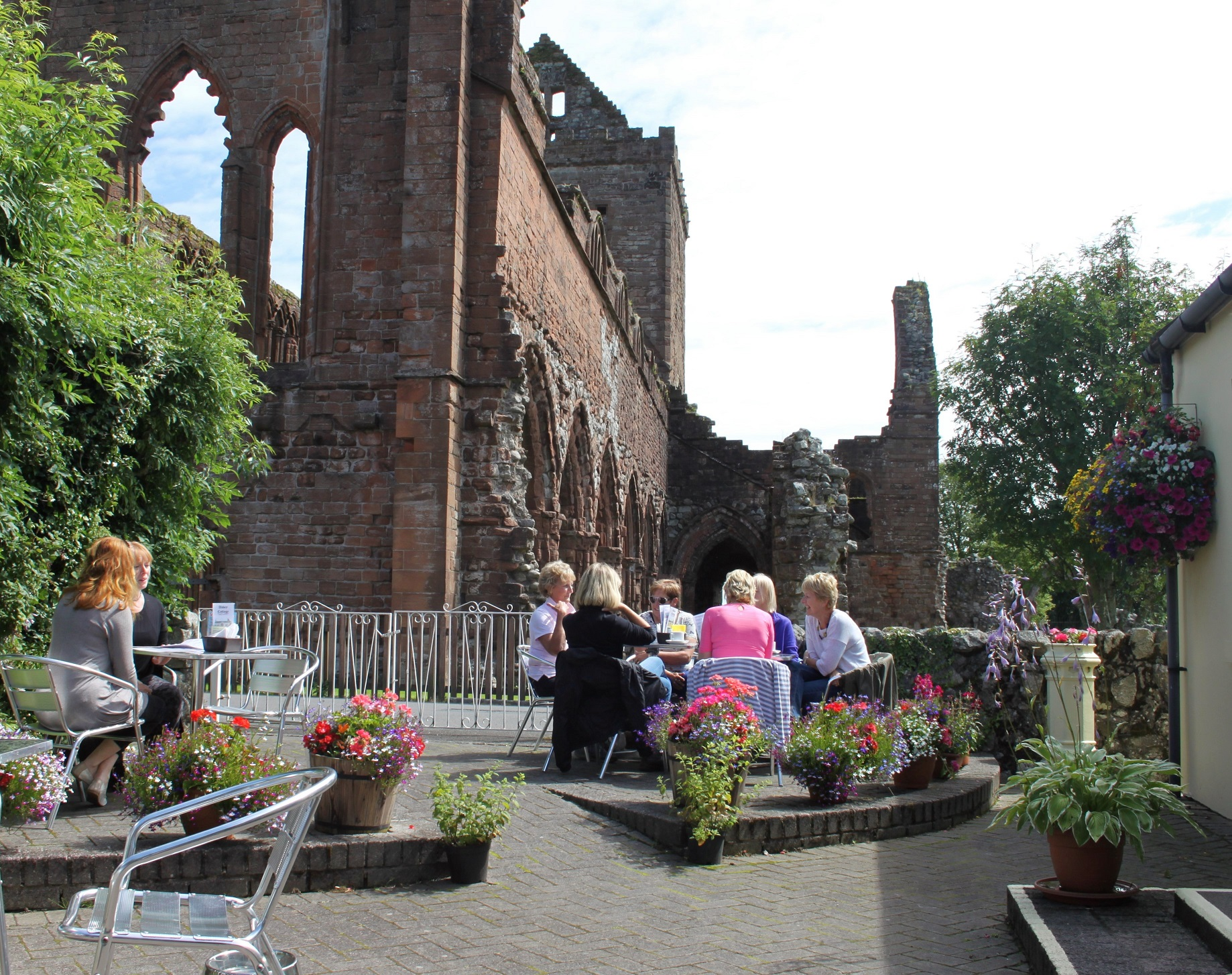 Afternoon Tea in the garden at Abbey Cottage Tearoom with a view of Sweetheart Abbey on the South West Coast 300